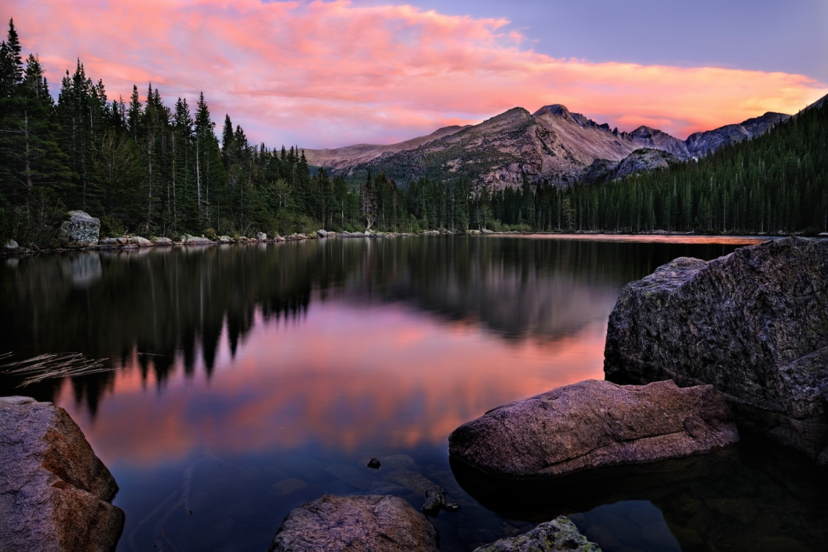 A mountain peak reflected in a lake as the sky turns pink