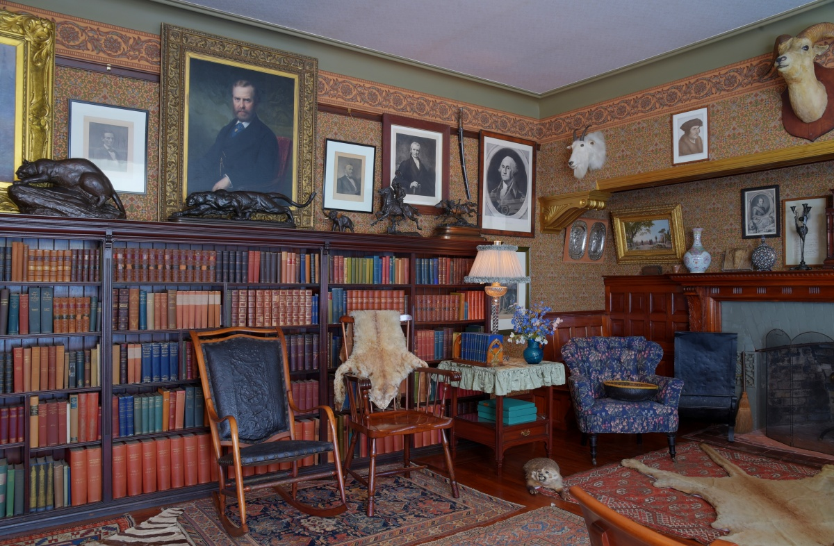 Picture of Theodore Roosevelt's library shows many bookshelves, paintings and mounted animals.