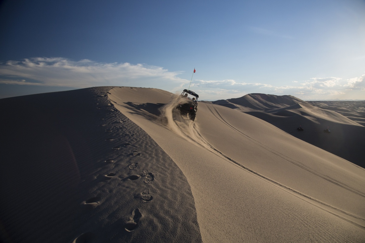 Off-roaders crest a hill on the St. Anthony Sand Dunes as the sun shines down.