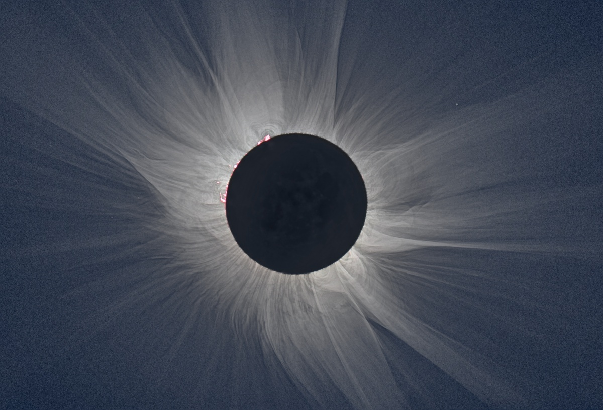The large black circle of the moon blocks the sun as light streams around its edges.