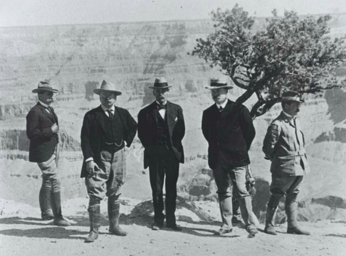 President Theodore Roosevelt and other officials pose in front of the Grand Canyon