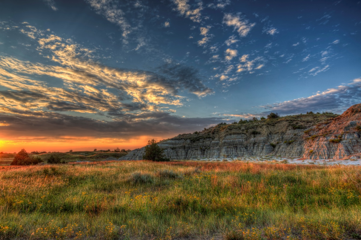 The sun sets over a green grassy plain with a colorful bluff rising in the background.
