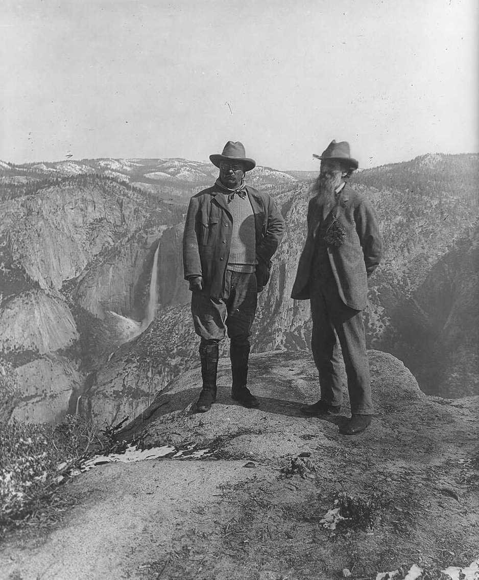 Theodore Roosevelt and John Muir stand on a rock cliff overlooking a valley and waterfall.