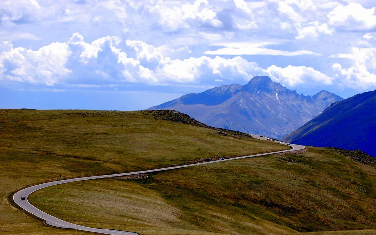 The trail ridge road cuts up the side of a hill with other mountains shooting into the clouds in the background.