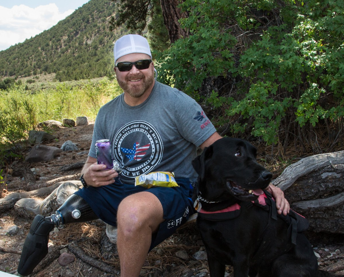 A man sits and snacks in the shade next to his Labrador Retriever on a fallen log.