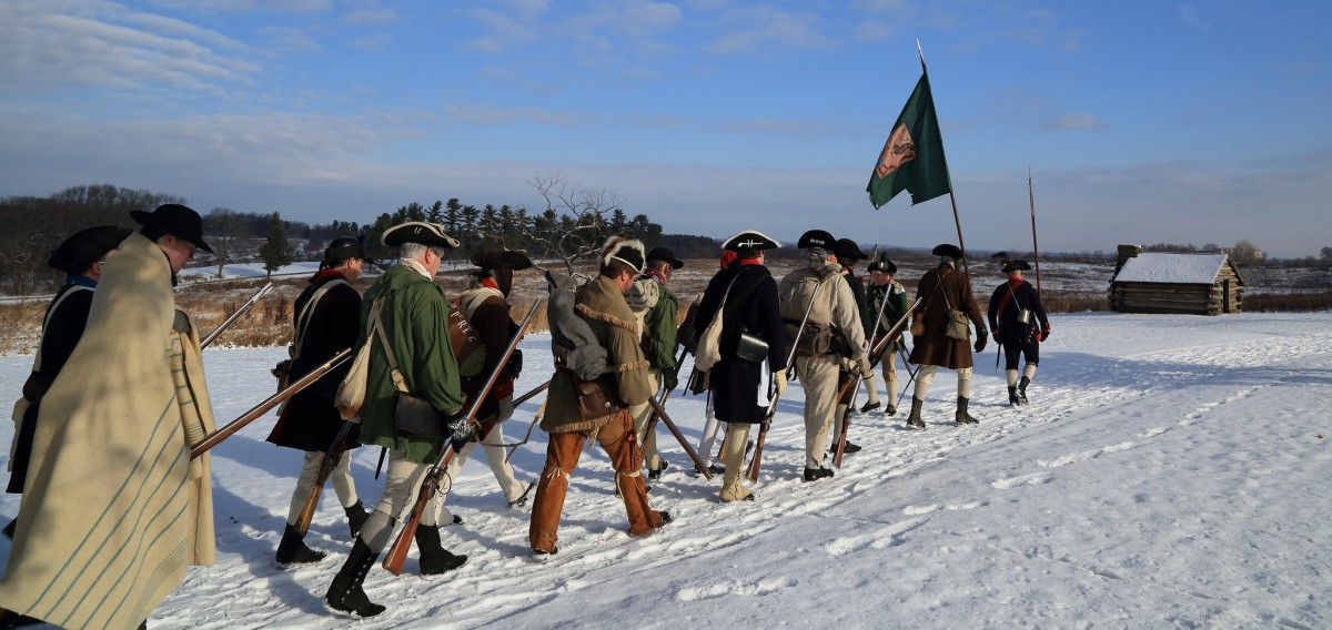 Valley Forge reenactors march through snow.