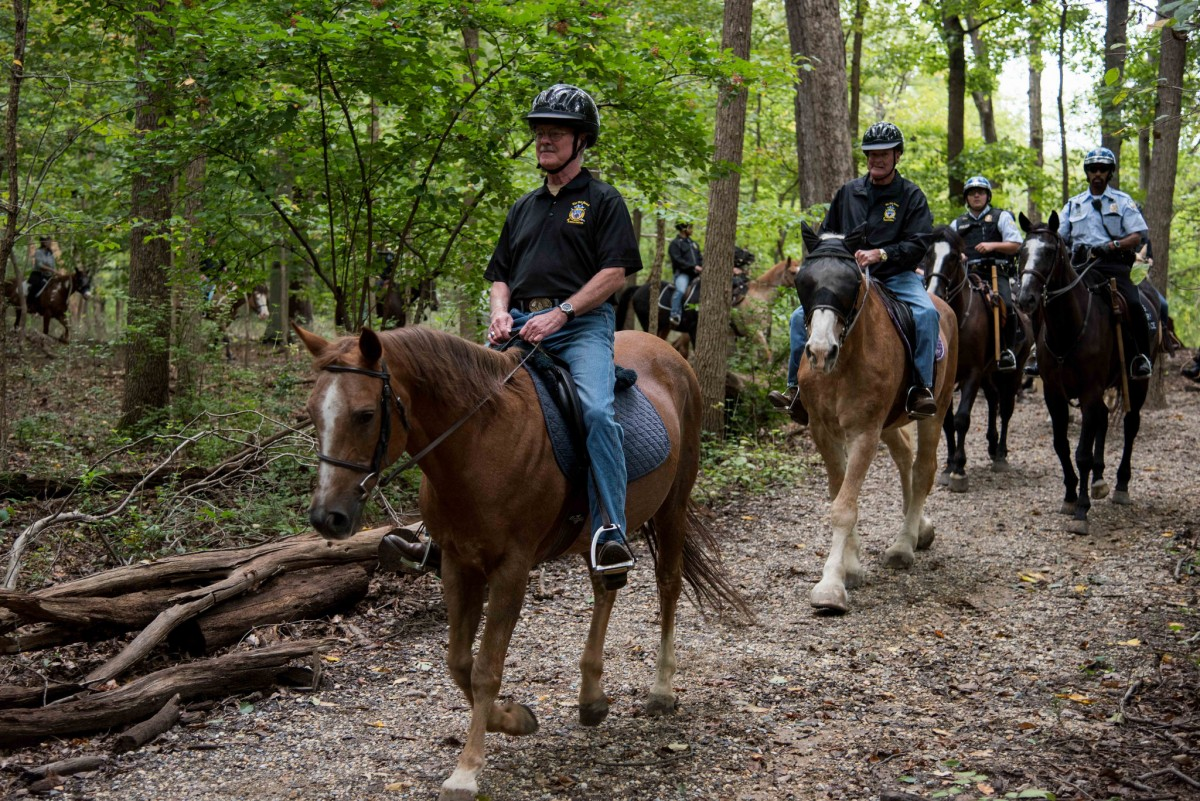 Veterans mounted on horses proudly walk in a line with Park Police on a path winding through tall green trees.