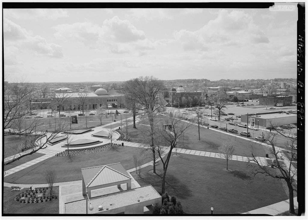 A black and white photo of a park with grassy areas and sidewalks leading to buildings across the street.