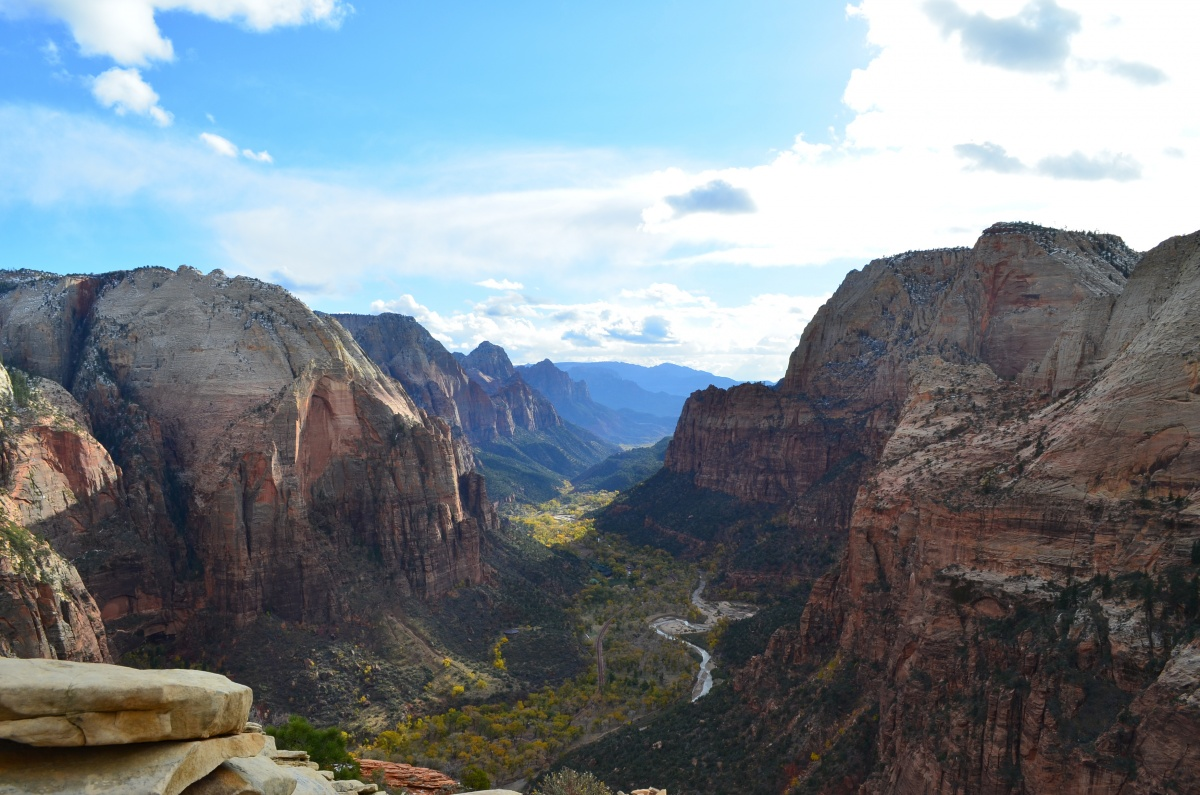 A view from Angel's Landing of the sharp red cliffs and small river cutting through a massive valley.