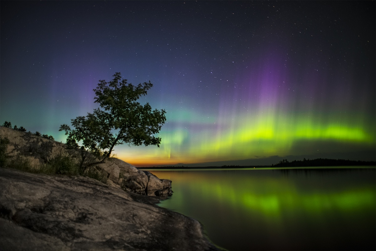 The green, blue, and orange Northern Lights appear to dance in the sky. The water below captures their reflection, and the stones along the river are illuminated in the light. A single tree reaches into the sky from the rock.