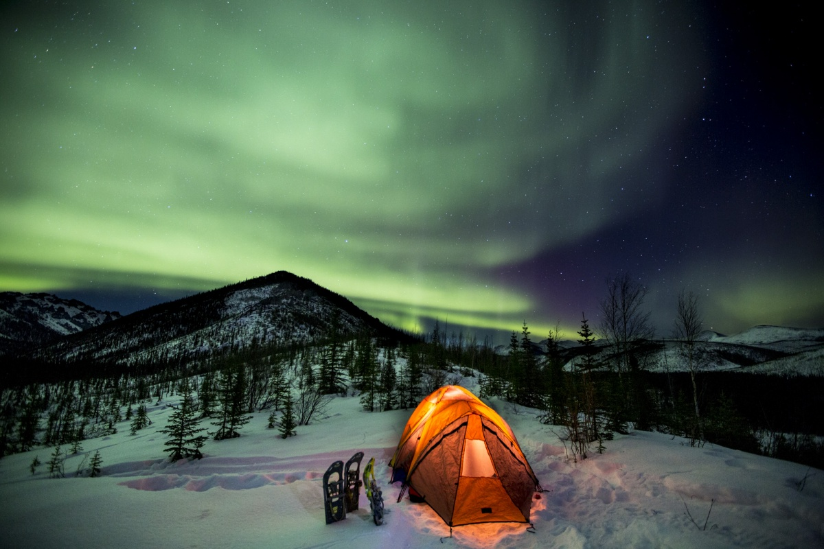 An orange tent glows in the snow below green Northern Lights that illuminate the hilly landscape around it.