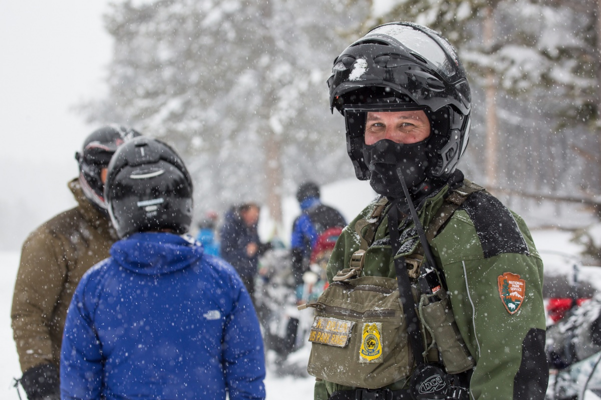 A white man in a National Park Service uniform and a large black helmet stands with a group of people wearing helmets and standing with snowmobiles in the snow.