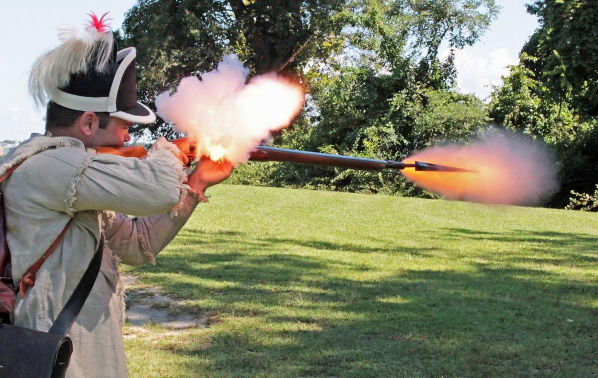 Reenactor fires musket.