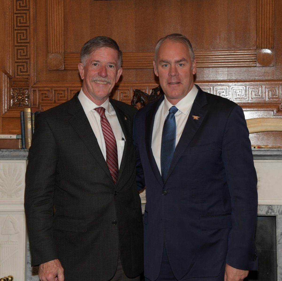 Secretary Zinke and Jim Reilly, both tall white men with gray hair wearing suits, pose together in a wood paneled office.