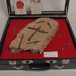 Objects associated with Saint Damien include a fragment of wood from Father Damien's redwood coffin, cloth, and nails from the Church of Our Lady of Seven Sorrows in Mapeluhu. (NPS)